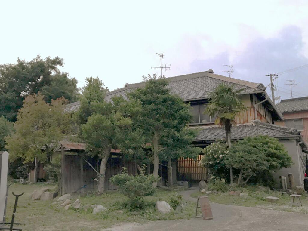 ますきちの正面。2階建て瓦葺きの古民家。年月を感じる大樹に包まれている。