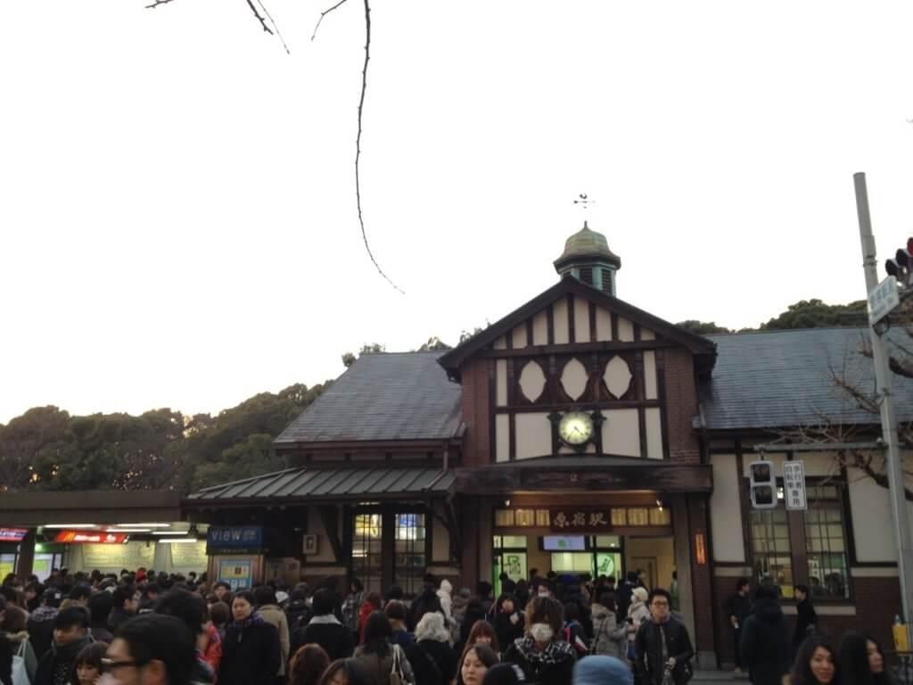 休日の夕方、人混みの中の原宿駅舎